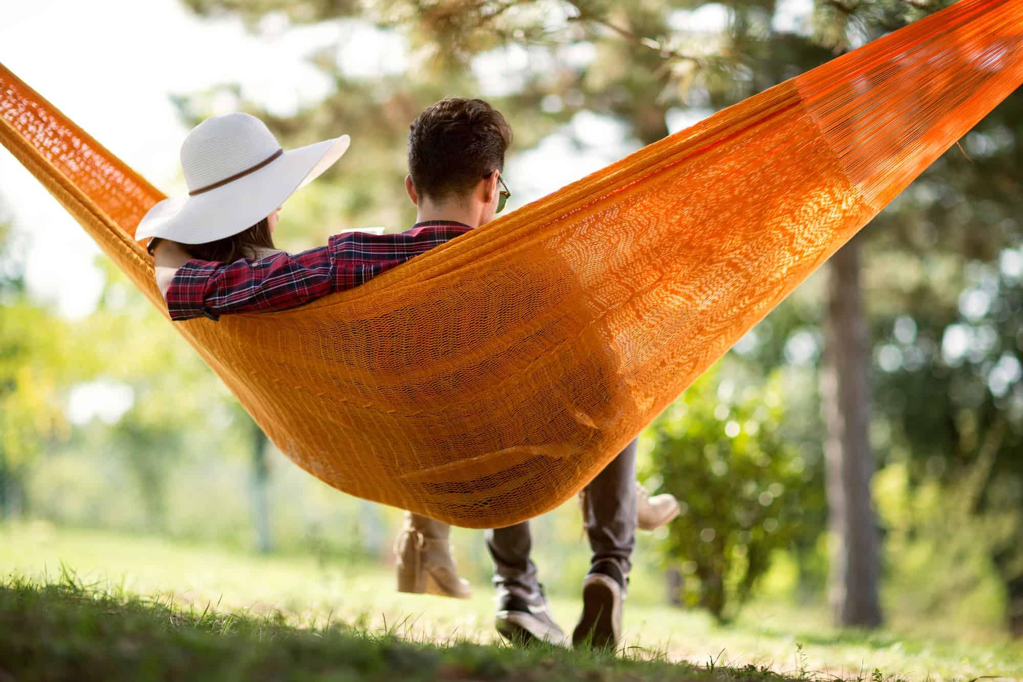 young couple enjoying at home date night in an orange hammock in their backyard