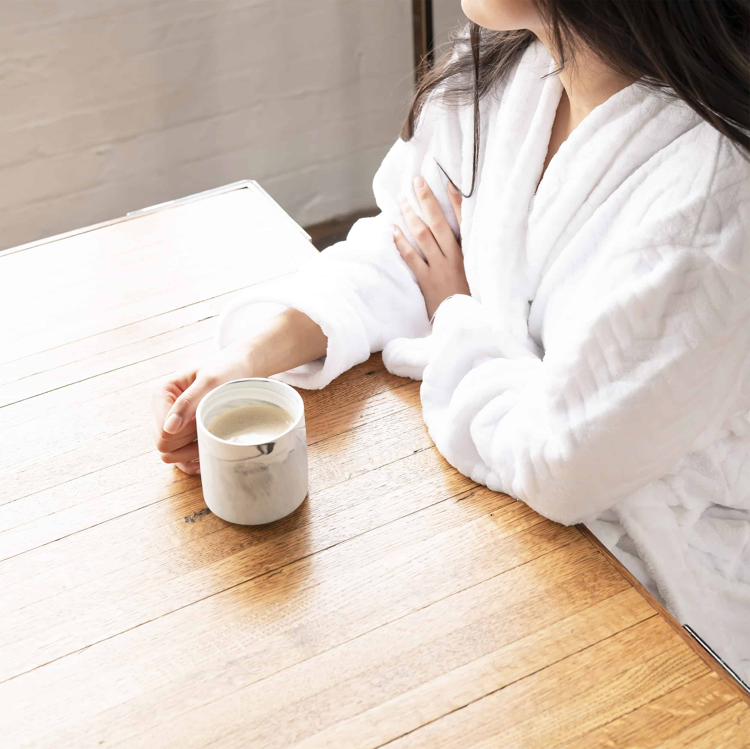 Woman sitting by window with cup of coffee, thinking about financial implications of divorce and whether or not to get a life insurance policy on her ex-spouse