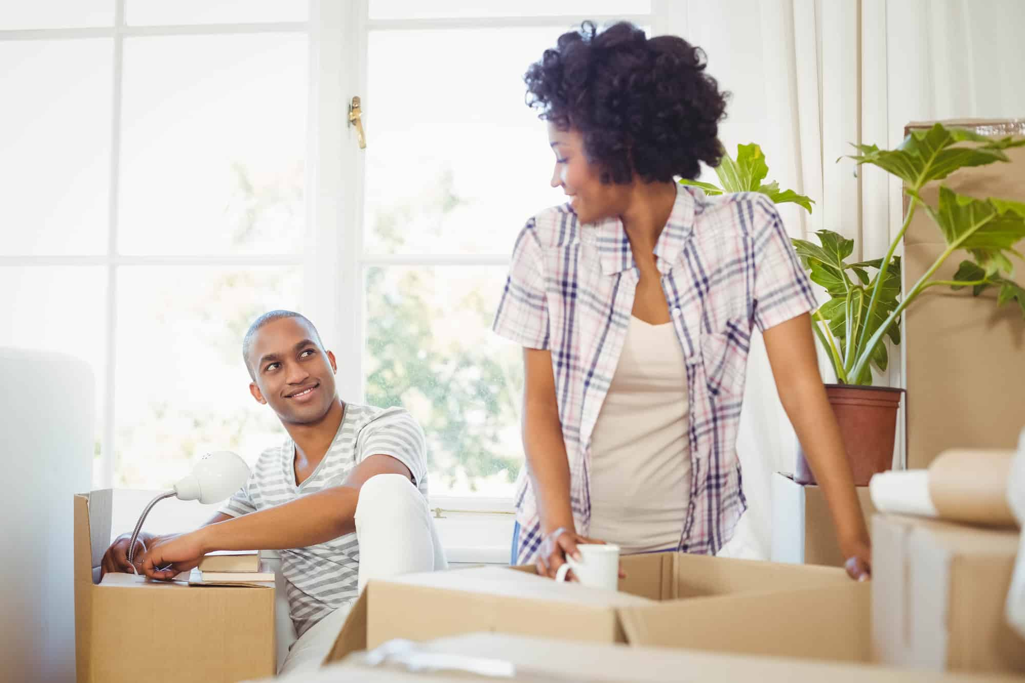happy couple unboxing belongings in new apartment, wondering how well they negotiated their rent