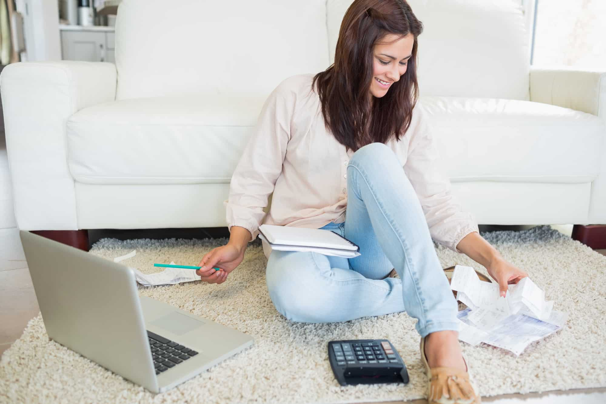 young woman sitting on carpet with bills and laptop, figuring out how to lower electric bill in apartment