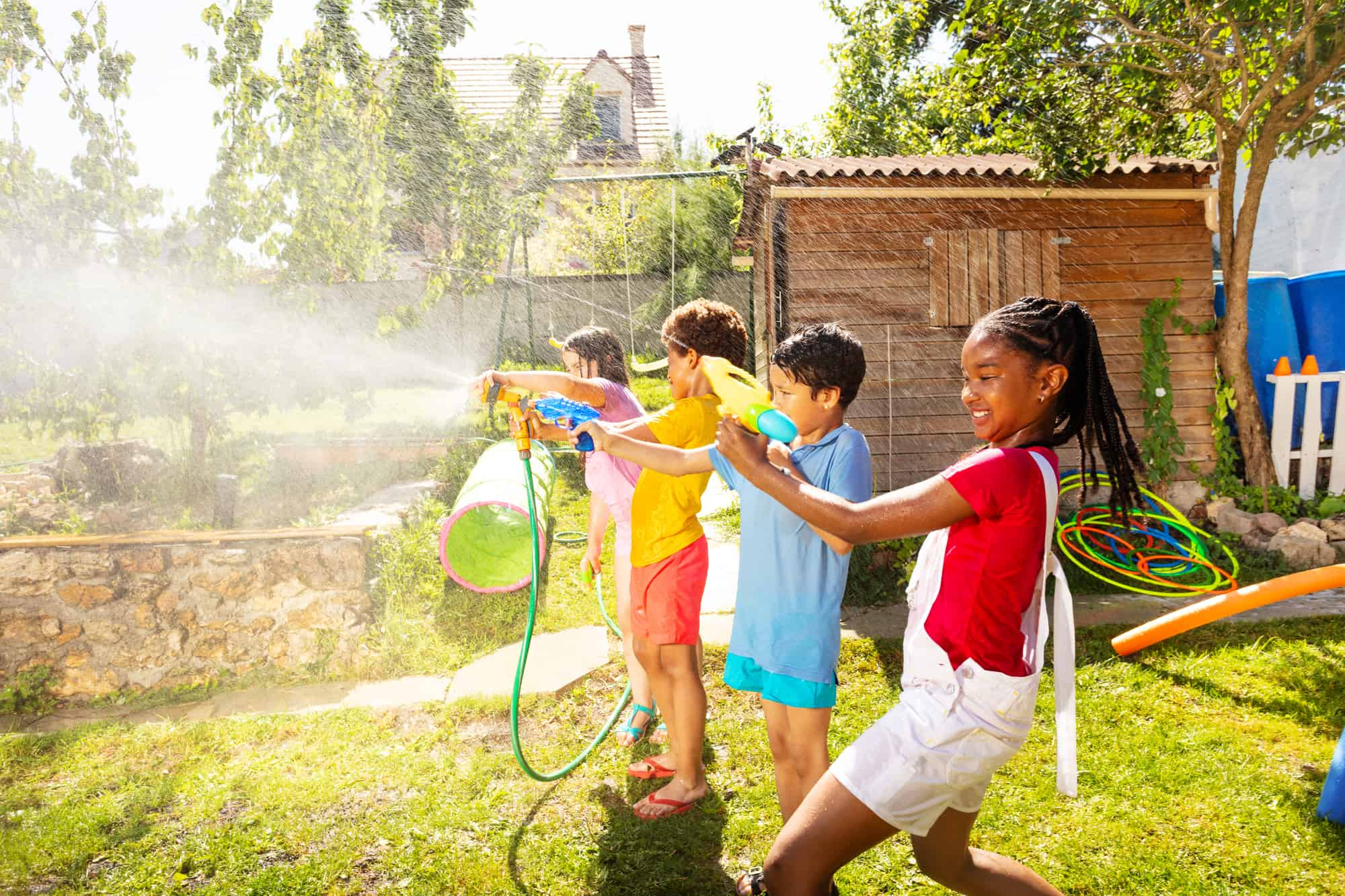 four kids with water guns playing in backyard activity for kids, outdoors