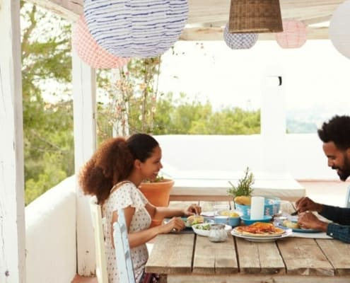 couple using outdoor date idea in backyard by eating dinner together on back patio- stay at home date ideas for couples