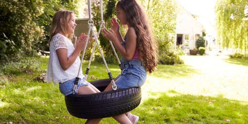 two girl kids swinging on a tire swing in their backyard, activities for kids