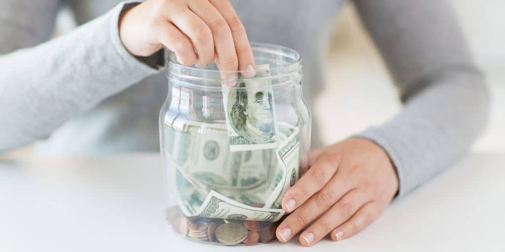 woman putting money into a money jar, wondering about money jar ideas she can use