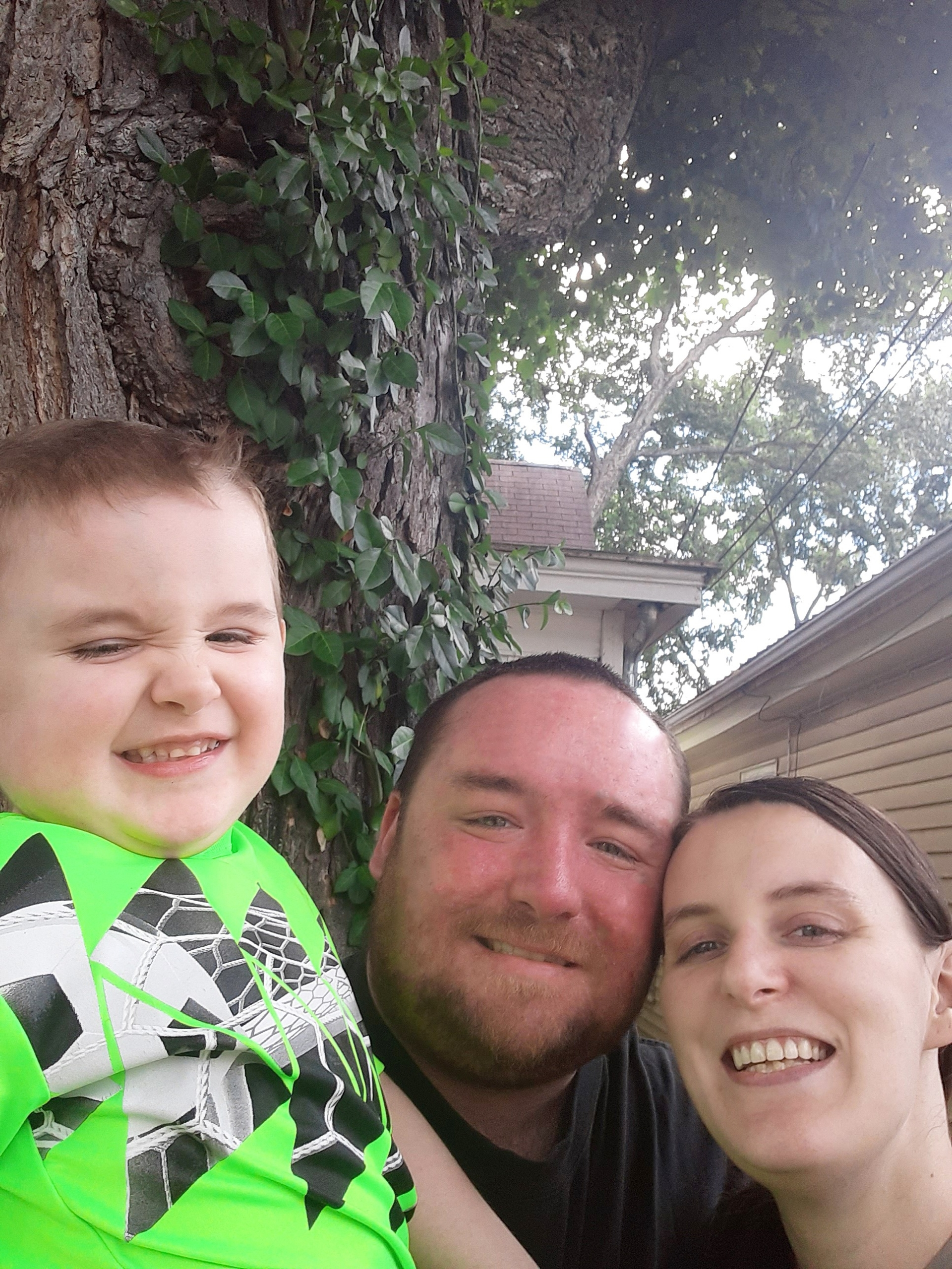 picture of Brittany and her husband and son in front of tree