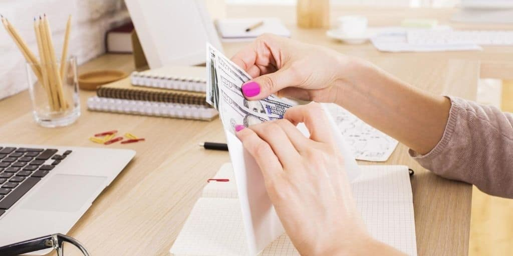 woman's hand stuffing budgeting envelopes free at desk