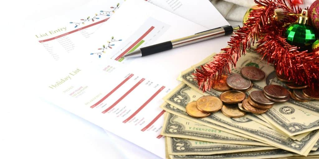 desktop with Christmas list printable, money, and Christmas decorations