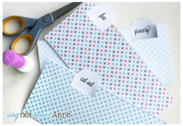 three cash envelopes with blue patterns on desk with scissors and marker