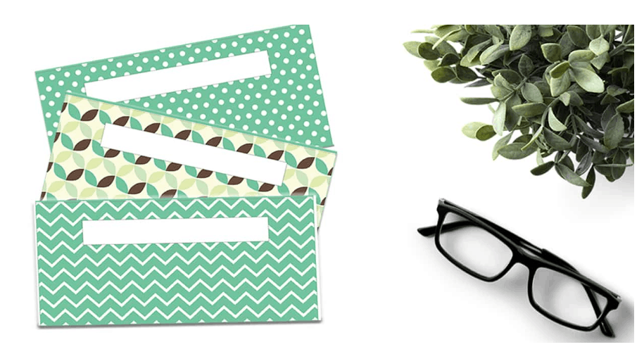 3 green patterned envelopes for cash with glasses on white background