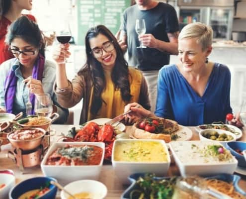 group of friends and family eating at table with main dish recipes for large groups