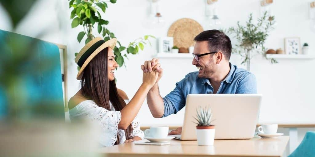 married couple slapping each other 5 in front of laptop, taking free online marriage counseling course