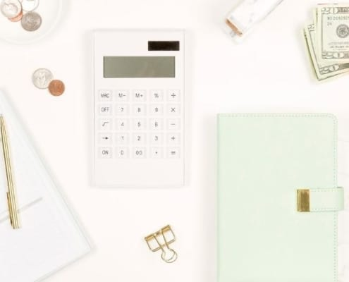 computer flat lay with calculator and notepad showing frugal examples