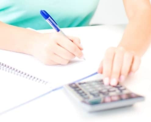 woman in blue shirt at desk, working on budgeting techniques and strategies with calculator
