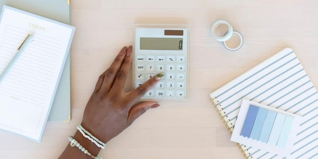 woman's hand using calculator and cute budget planner worksheets at desk