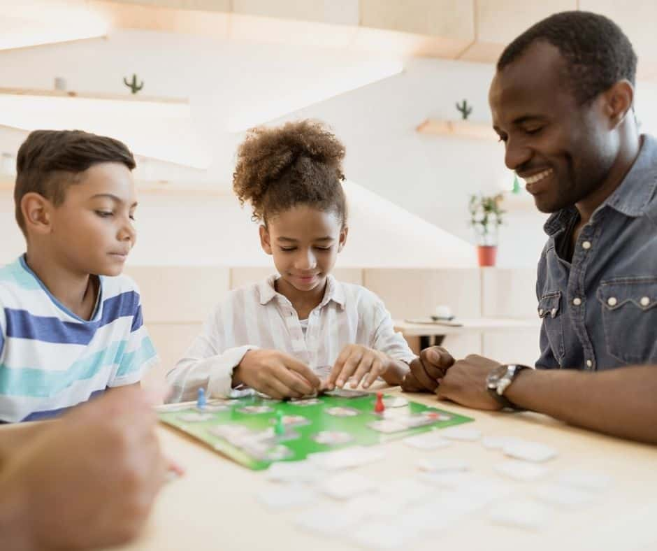 family with father and two kids playing board game together as family bonding activity