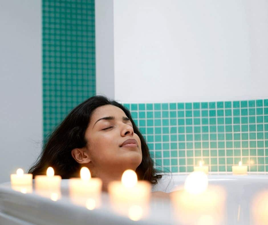 woman sitting back, relaxing in bath tub surrounded by candles as a small daily rewards