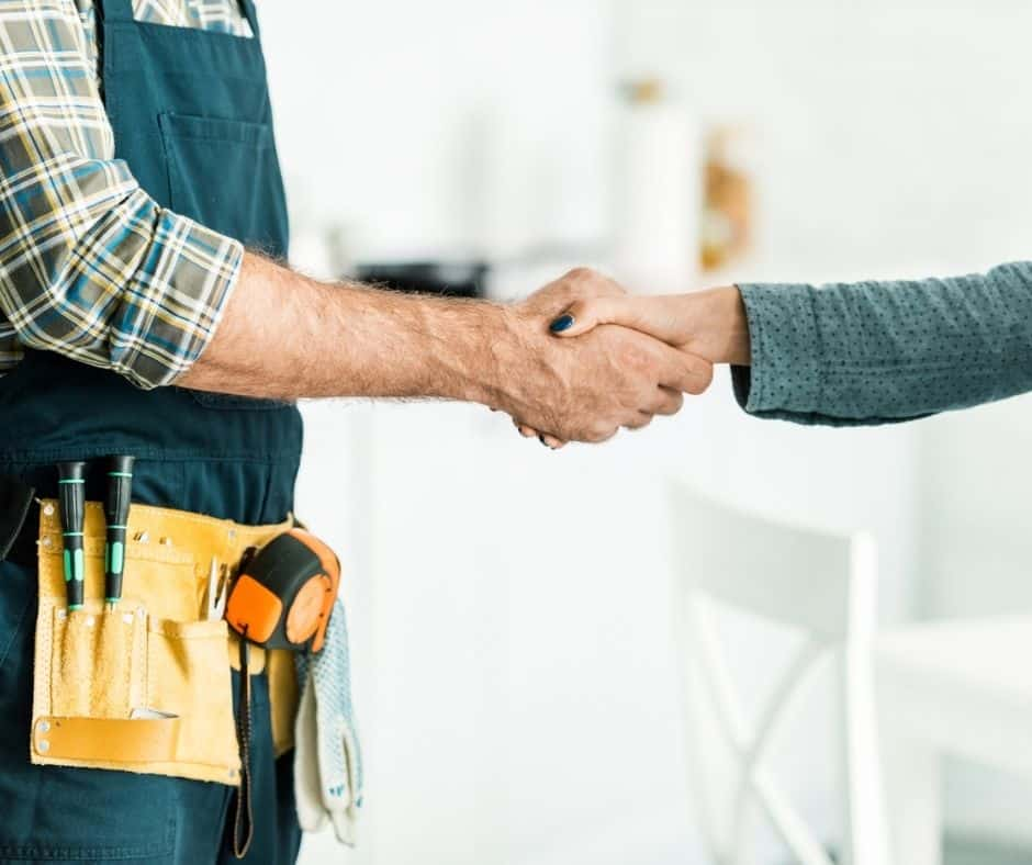 woman shaking hands with contractor - how to negotiate with contractors