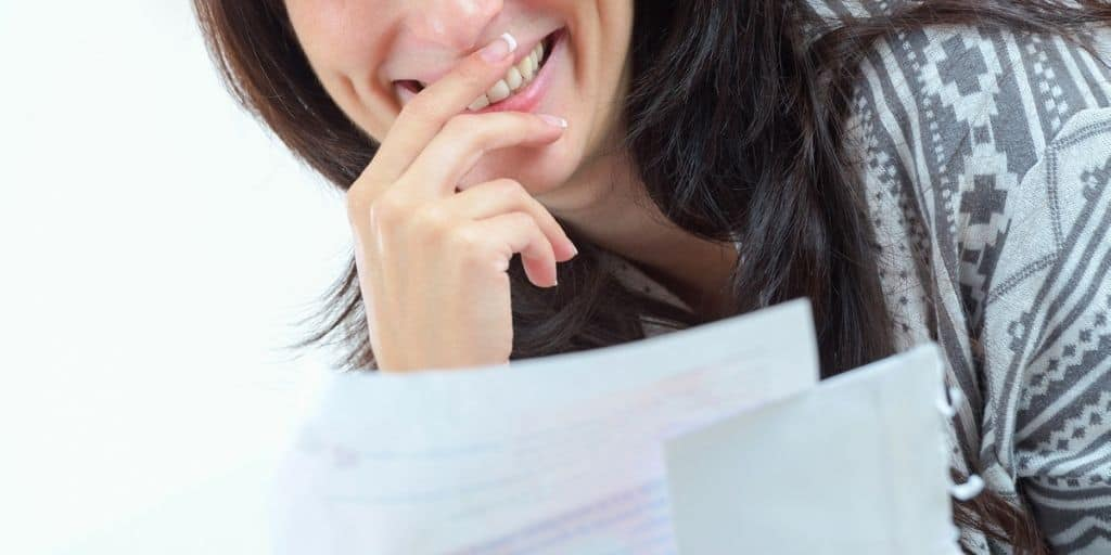 woman looking surprised at paper bills with how to reduce household expenses