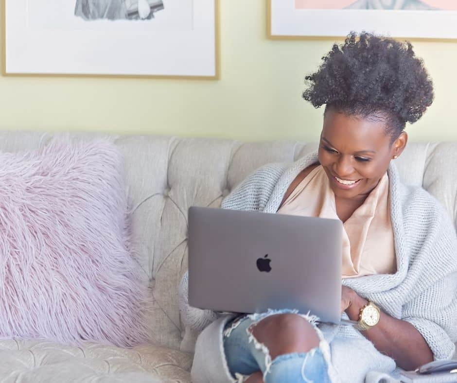 woman smiling on laptop on sofa with purple pillow, finding ways for how do you stop spending online