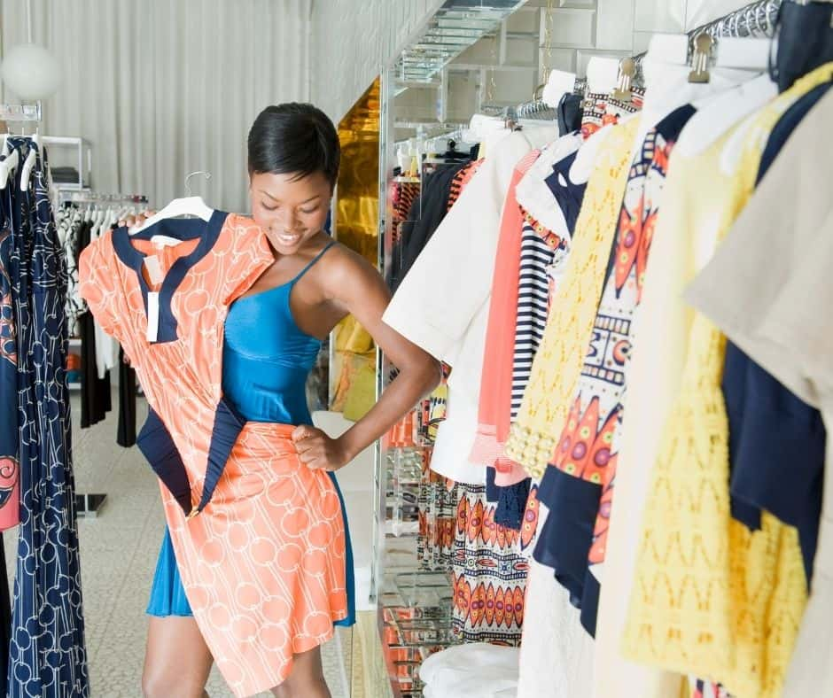 woman buying clothes at a store with big smile on her face, knowing How to Spend Less Money on Clothes