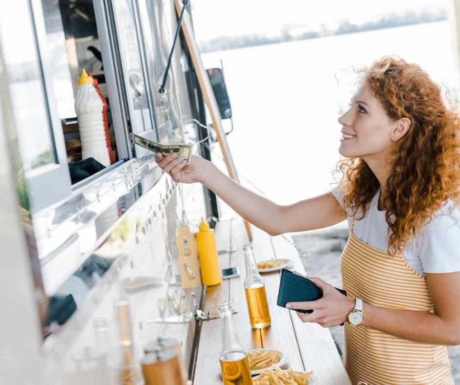 woman handing money to someone in a food truck, thinking about How to Spend Less Money on Food