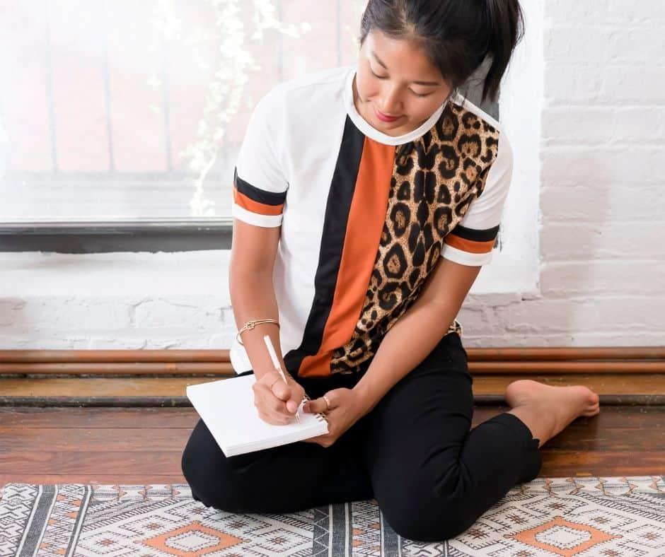 Asian woman doing abundance mindset exercises in her journal
