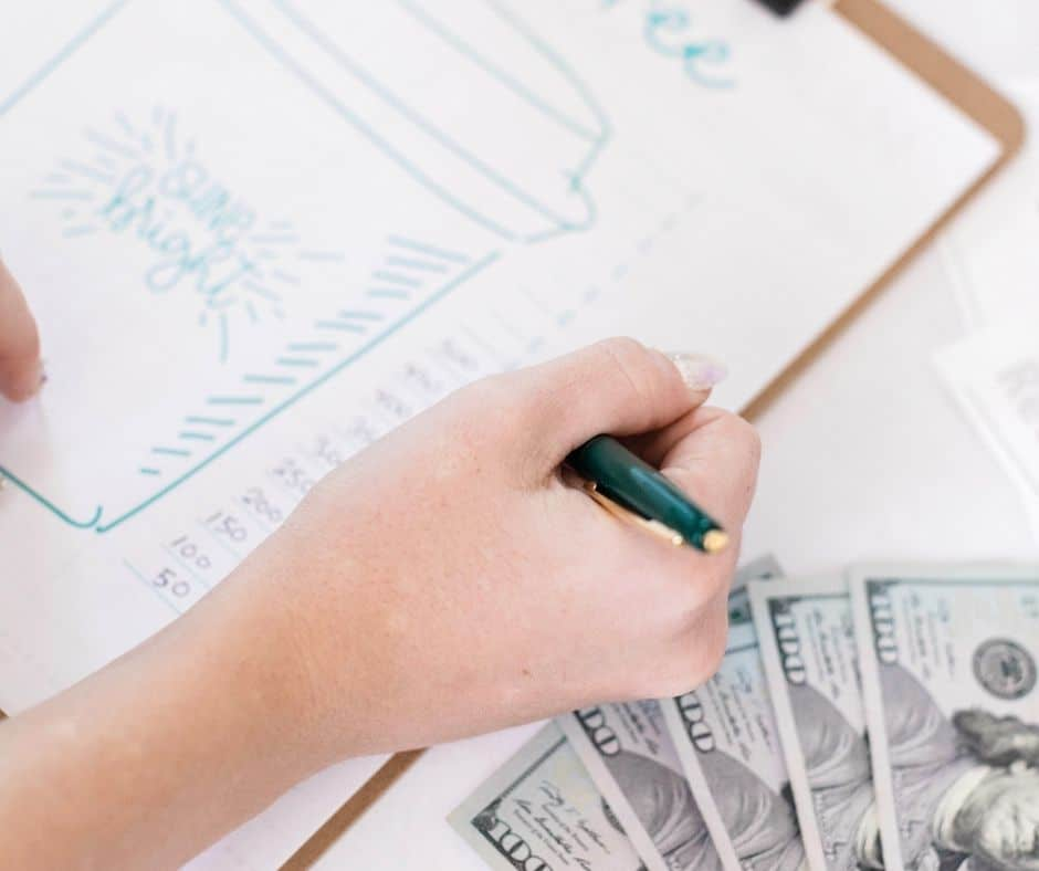 woman working on her spending audit from the previous year, with clipboard and money by her side