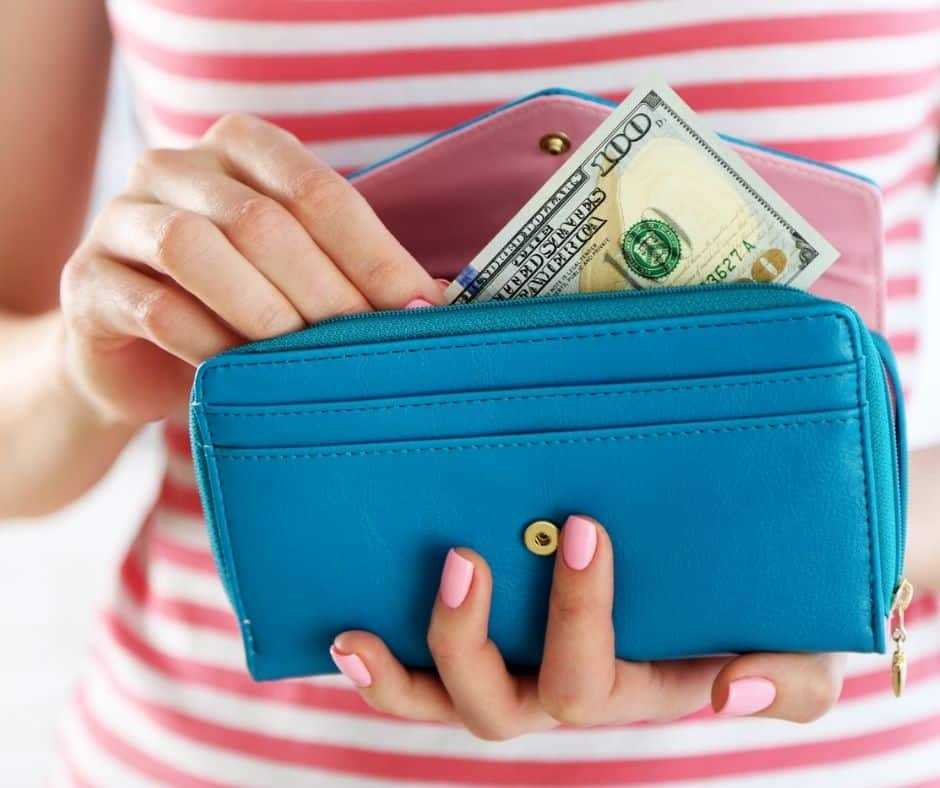 woman in striped shirt with wallet and money, checking in with her finances to help how to stop spending money you don't have