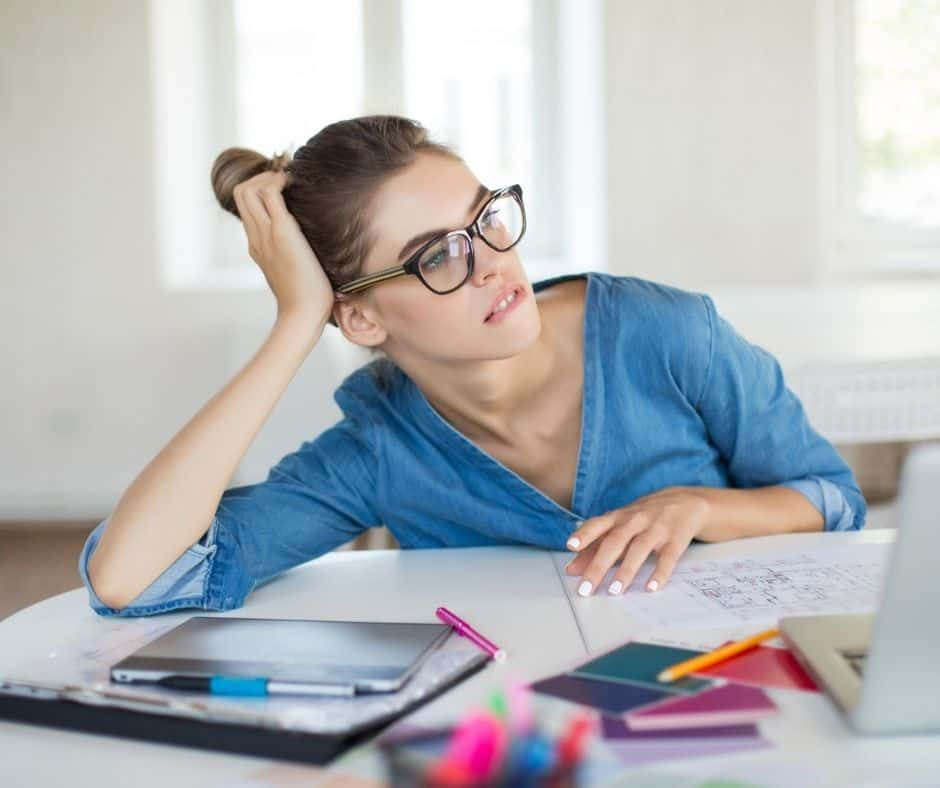 woman looking reflectively at her spending at desk, wondering how to train yourself to spend less money