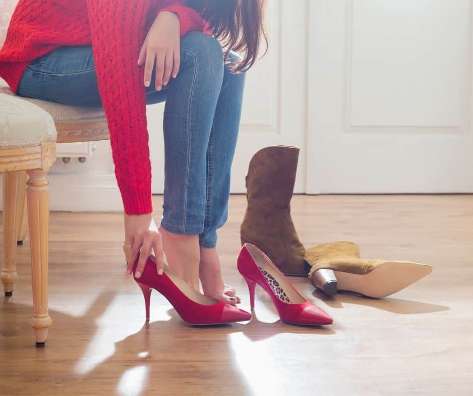 woman trying on red high heels, wondering what the psychological reasons for overspending are