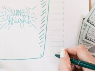 money on desk next to woman's hand writing on emergency fund tracker printable