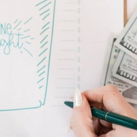woman's hand writing in 1000 emergency fund tracker printable, with cash on her side