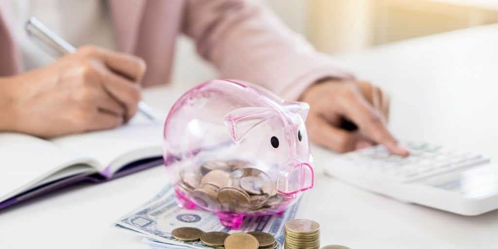 woman with pink piggy bank and calculator on desk, working on a no spend challenge rules list