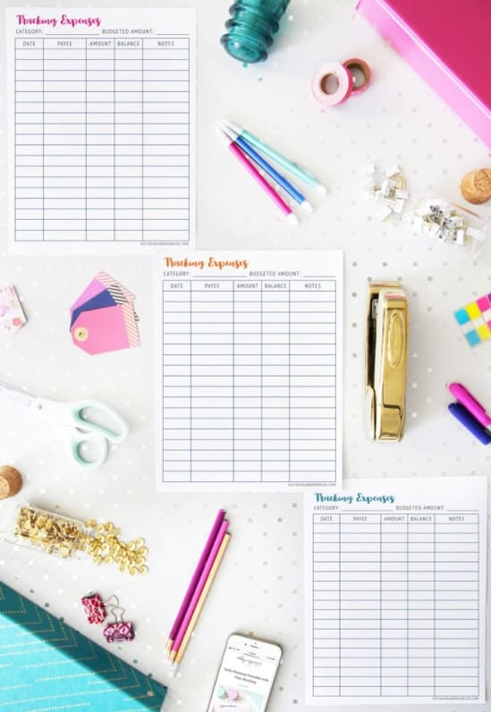 three monthly expenses trackers on white desk with lots of colorful elements like pens and staplers and stickers