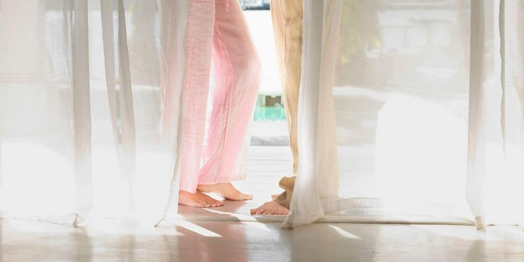 couple's legs in linen pants, on patio with door open and shimmery curtains
