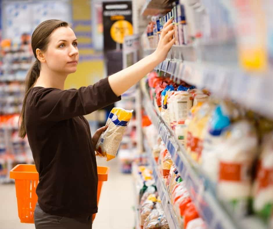 young woman with shopping basket picking out which cheese to buy, and not fall for supermarket tricks
