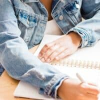 woman in jean jacket at wooden desk filling in a budget sheet notepad