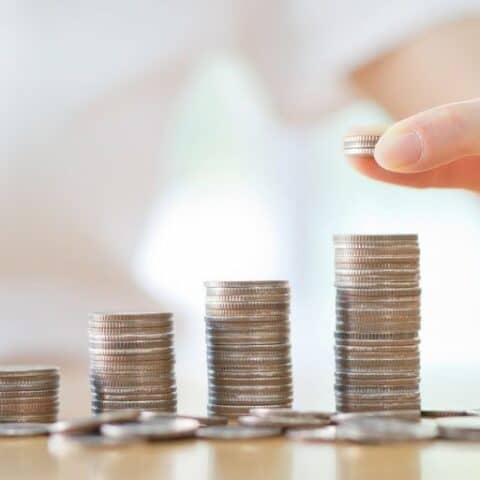 a hand counting a several towers of quarters on a wooden table, saving money on low paying job