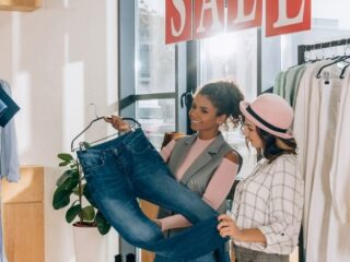 three women shopping a clothes sale wondering if they'll have buyer's remorse after buying a pair of jeans