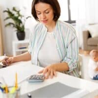 middle aged woman with calculator and laptop filing taxes at desk