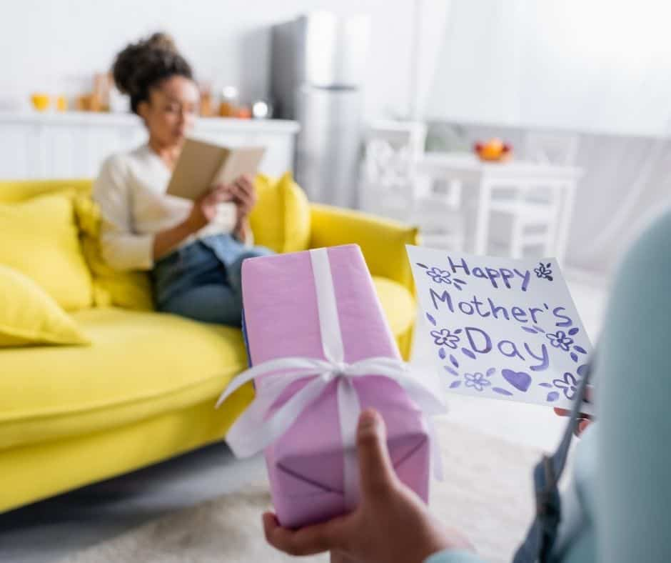 child surprising unsuspecting mother sitting on couch reading with purple-wrapped gift, for gifts for mom who has everything
