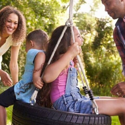 family of four laughing and playing on a tire swing out back as a way to cut family expenses