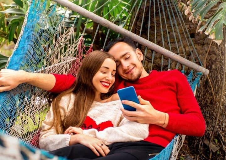 young couple in red and white shirts on a hammock, smiling, looking at summer couple activities on their phone