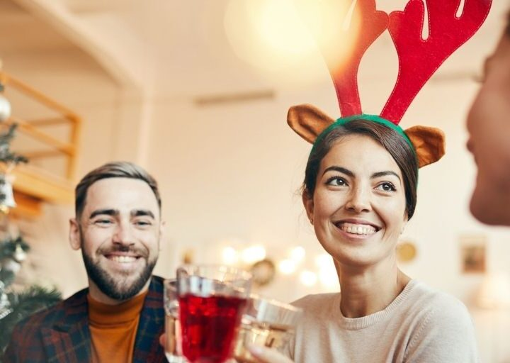 man and woman with Rudolph antlers in front of tree, smiling while doing adult Christmas Eve traditions