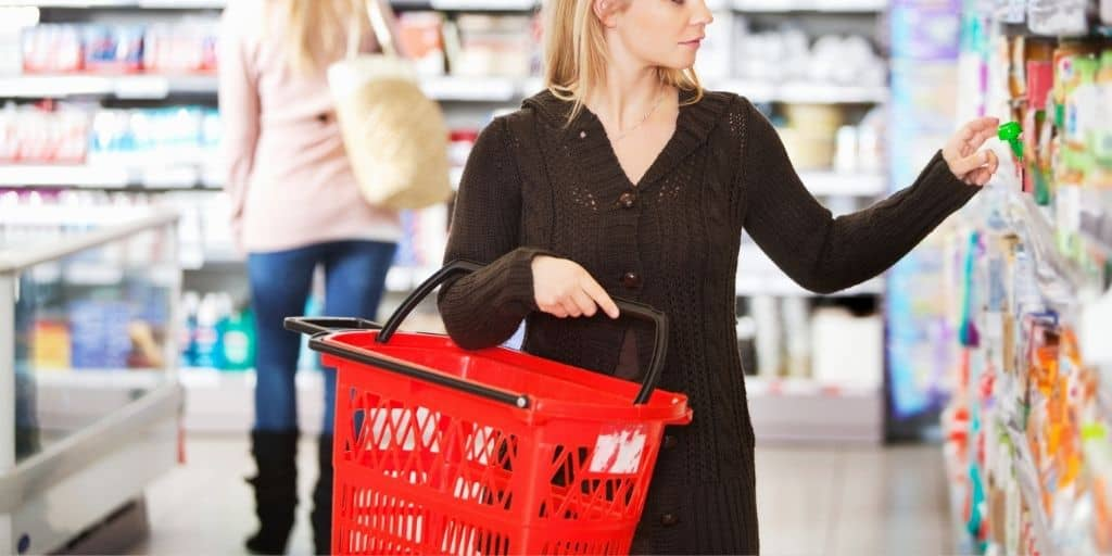 woman with shopping basket at store, making decision for what to buy - types of spending habits