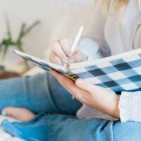 woman in jeans on bed writing her smart financial goals in journal