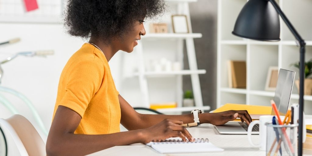 young woman in yellow shirt at desk, thinking about which financial goal category she wants to go after