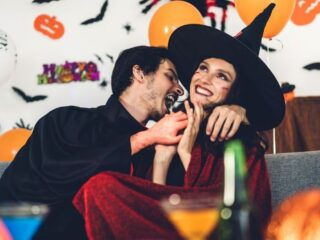 adult couple on couch dressed in Halloween costumes, giggling for things adults can do for halloween
