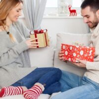 couple exchanging Christmas eve boxes for adults on white couch