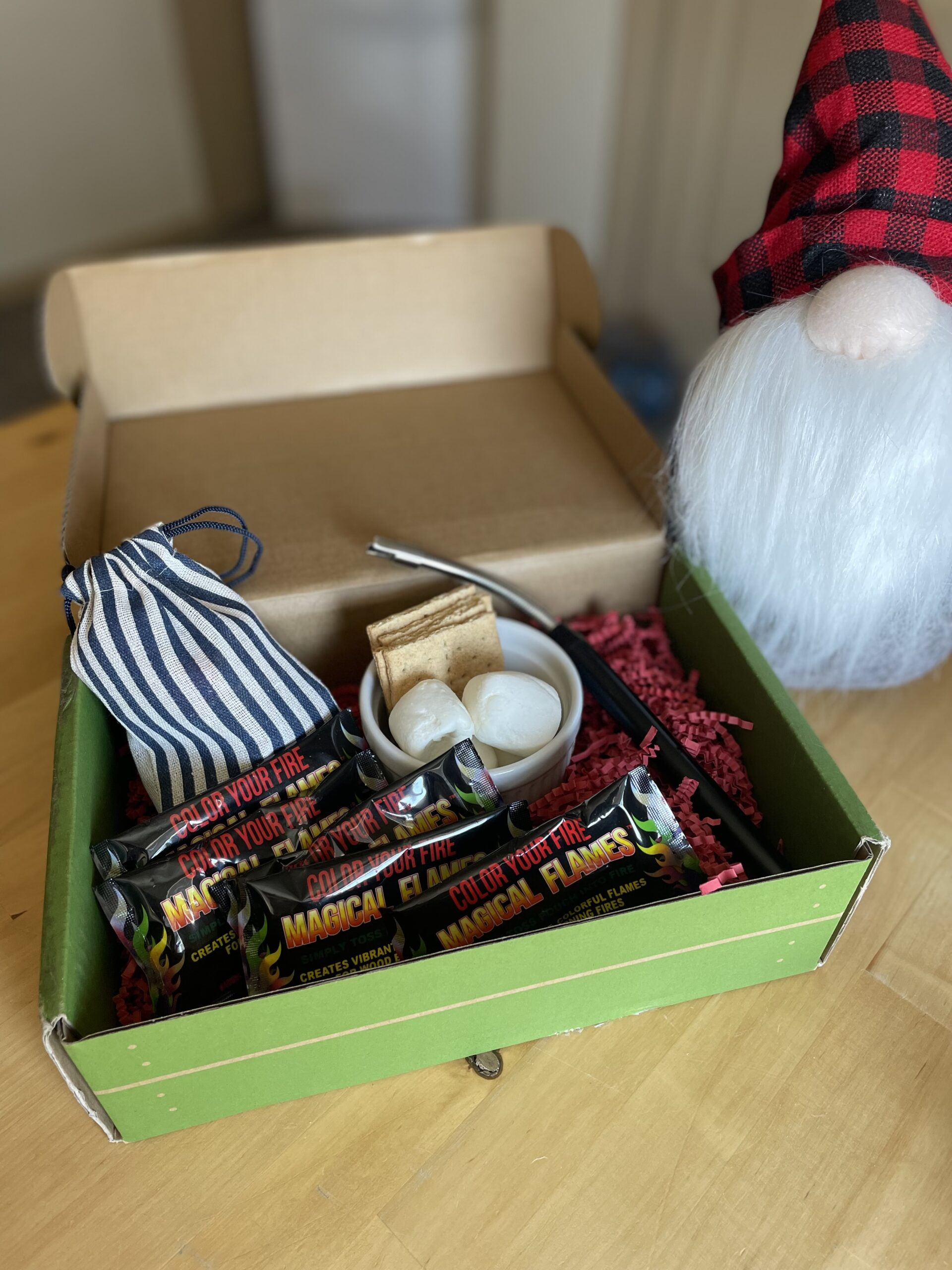 green box with red stuffing, arc fire lighter, treat sack, fire colorant packages, and marshmallows and graham crackers in a little ramekin